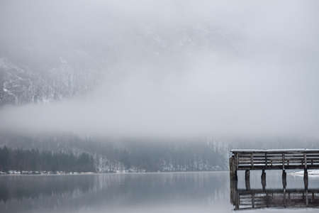 Wooden pier at lake Bohinj reflecting in still water with mountains in background.