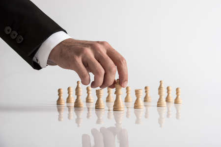 Conceptual image of human hand wearing business suit moving queen chess piece at white table.