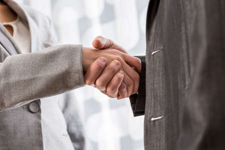 Low angle closeup view of male and female business partners shaking hands.