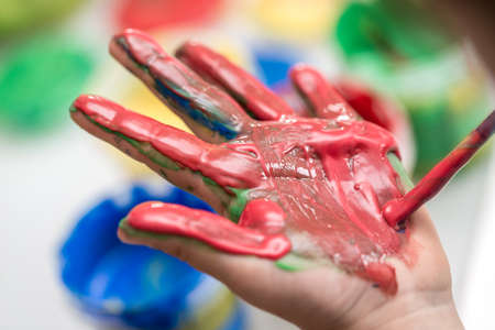 Closeup of a palm of a toddler being painted with thick red hand paint. Stock Photo - 107582722
