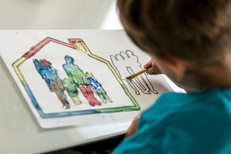 Child colouring in a sketch of a family using a paintbrush and watercolour paints. Reklamní fotografie
