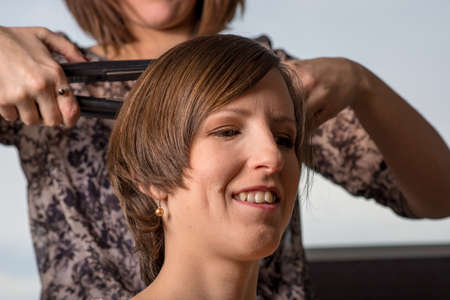 Portrait of a young smiling woman sitting at hairdresser while she is straightening her brown hair. Standard-Bild - 107700183