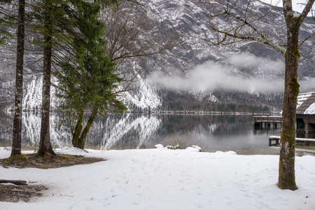 Winter scene at beautiful lake Bohinj with mountains in background and mist over the lake.