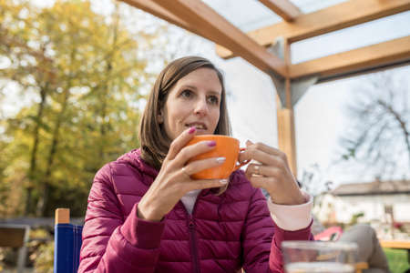 Young woman drinking coffee in orange cup sitting outdoors in autumn day wearing purple jacket.