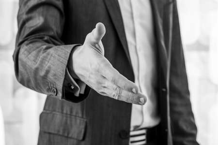 Black and white image of a businessman in a suit offering his hand in handshake. Closeup view. Фото со стока