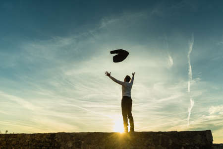 Happy successful businessman celebrating standing on the skyline on a wall silhouetted against the sun with copy space tossing his jacket in the air with outspread arms.