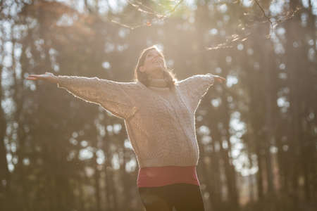 Young pregnant woman enjoying her last trimester of pregnancy outside in an autumn forest with arms outstretched.