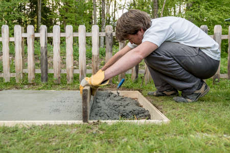 Young man leveling cement in a backyard using wooden plank laying new concrete foundation in a diy concept. Banco de Imagens