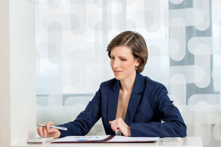 Young female accountant sitting at her desk using calculator with statistical report and charts in a folder in front of her. Stock Photo