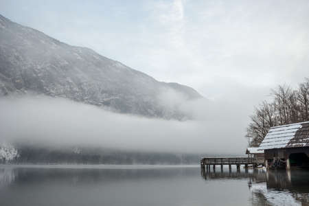 Wooden pier on winter lake Bohinj with mist above it and mountains in background.