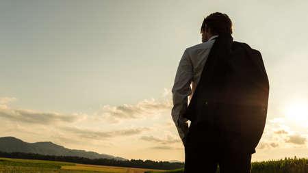 Blick von hinten auf einen Geschäftsmann, der mit einer Jacke über der Schulter steht und die schöne Natur von Maisfeldern und Wiesen betrachtet.