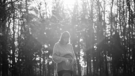 Black and white image of young pregnant woman in last trimester making heart shape with her palms on a belly while walking in autumn forest.
