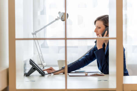 View through an office partition of a young businesswoman or secretary dialing a phone number on a black landline telephone.