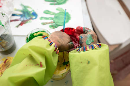 Closeup view of little hands scooping and mixing colourful finger paints from jars making palm prints.