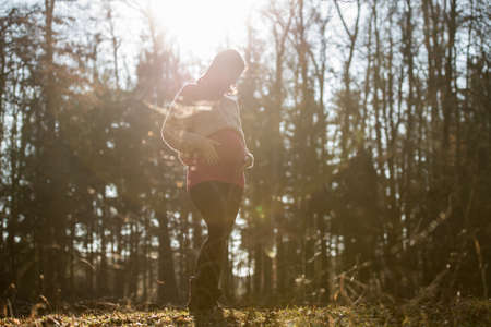 Young pregnant woman in last trimester standing in autumn forest lovingly touching her belly with sun flare coming through the trees.