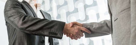 Closeup view of business man and woman shaking hands in greeting or agreement. Wide view image.