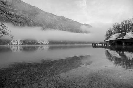 Mystical winter nature with wooden pier on beautiful lake Bohinj, mountains in background and white mist above the water. Imagens - 108771364