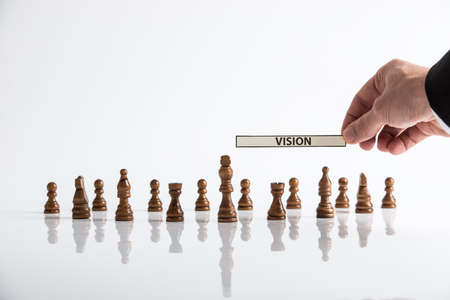 Chess pieces places on white glass desk with businessman holding a paper with the word vision above the figures.