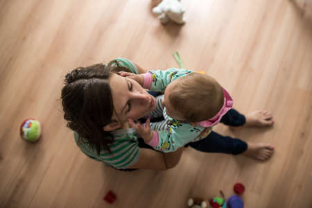Top view of young mother sitting on wooden floor playing with her baby girl.