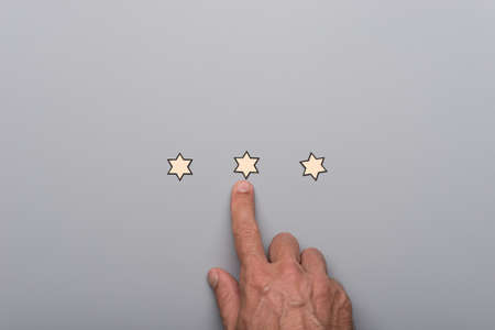 Male hand pointing at on of three paper cut stars placed in a line over grey background.