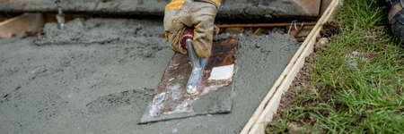 Closeup of gloved hand smoothing fresh concrete surface outside in a wide view image. Imagens