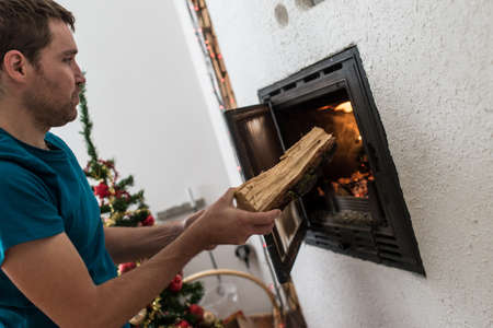 Young man putting a wooden log in a fireplace at home with decorated christmass tree in background.