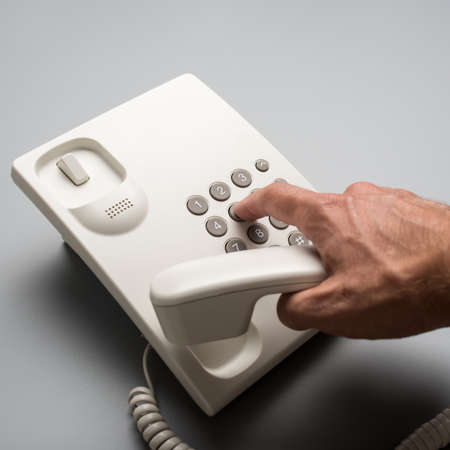 Male hand dialing telephone number using white landline phone, over grey background.