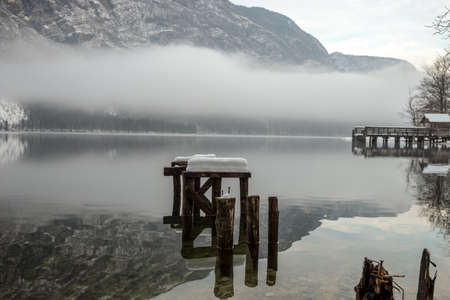 Decaying wooden pier in winter lake Bohinj with mountains in background and myst above the water.