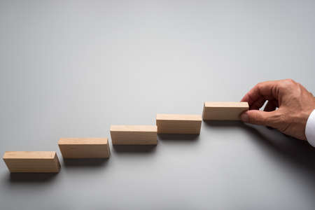 Zakenman die houten pinnen of domino's op een grijze ondergrond plaatst. Conceptueel van bedrijfsvisie en opstarten.
