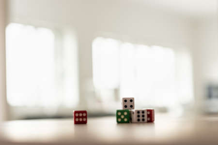 Gaming dice stacked on desk in a bright office. Archivio Fotografico