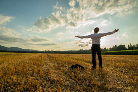 Businessman standing with his arms outstretched in a harvested wheat field under autumn sky.