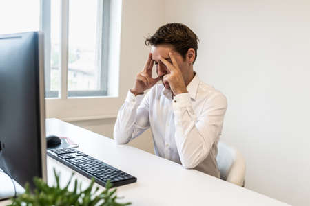 Frustrated businessman sitting at his office desk in front of computer leaning his head in hands.