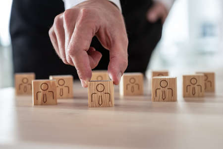 Human resources concept - businessman arranging wooden cubes with people icon on office desk. Archivio Fotografico
