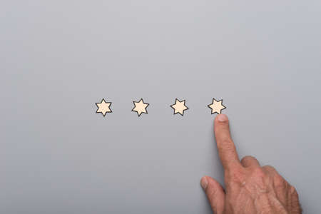 Male hand pointing to the last of four paper cut stars placed in a row on grey background. 版權商用圖片