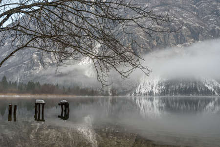 Decaying wooden planks of an old pier on a lake Bohinj in cold winter season. Imagens