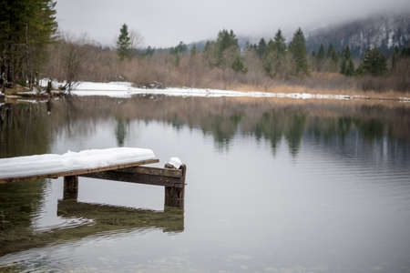 Lake Bohinj in winter with decaying wooden pier and nature reflecting in the water. Imagens