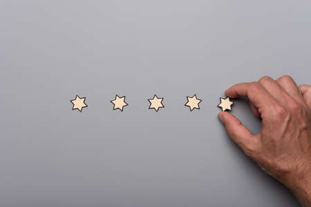 Male hand placing five paper cut stars in a line over grey background. Conceptual of business quality and guarantee.