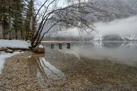 Beautiful winter landscape with peaceful lake, trees and mountains in misty background.
