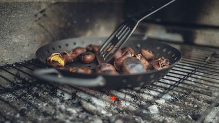 Closeup of roasting chestnuts above embers.
