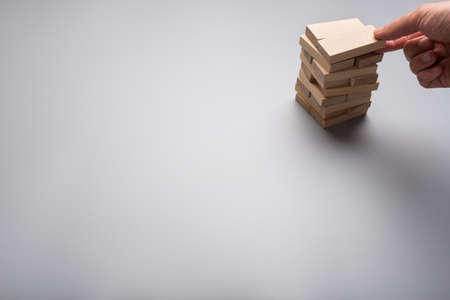 Businessman making a stack of wooden blocks in a conceptual image of business start up with copy space.