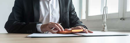 Economy and finance concept - financial advisor sitting at his desk making calculations on orange calculator. Imagens