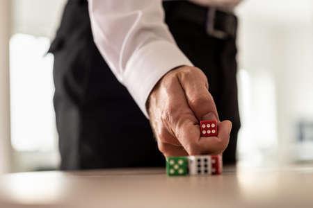 Concept de défi et de risque d'entreprise - homme d'affaires jetant des dés rouges sur un bureau.