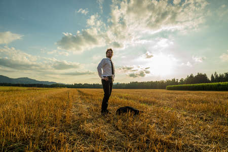 Young confident businessman standing in sawn field on a beautiful autumn evening under cloudy sky. 스톡 콘텐츠