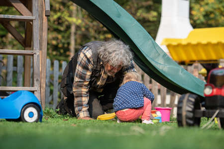 Grandpa playing with his granddaughter outside in backyard as they sit on the grass under a slide and play with sand toys and buckets. 写真素材
