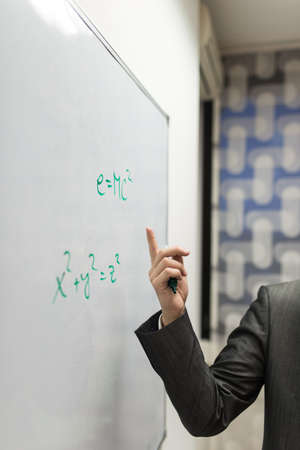 Closeup of professor pointing to a mass energy equivalence formula written on a white board.
