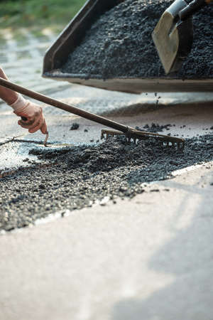 Closeup view of worker paving the road with asphalt as they level the cement mix.
