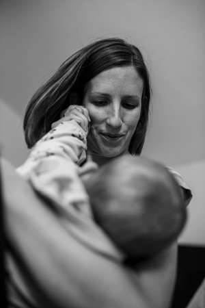 Monochrome image of young mother lovingly holding her baby and playing with her little hand. Stockfoto