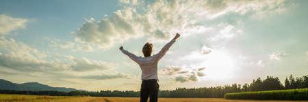 Image panoramique d'homme d'affaires prospère debout sous un ciel majestueux avec ses bras levés haut en triomphe.