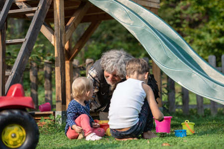 Grandfather sitting in a grass playing with his two grandchildren in a playground.