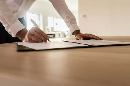 Businessman standing at his desk leaning to sign a legal or insurance document in an open folder. Stock fotó